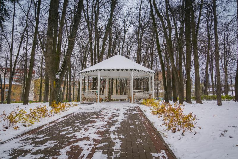 Winter White Alcove. Decorative wooden alcove with benches in the city park at the winter time stock images