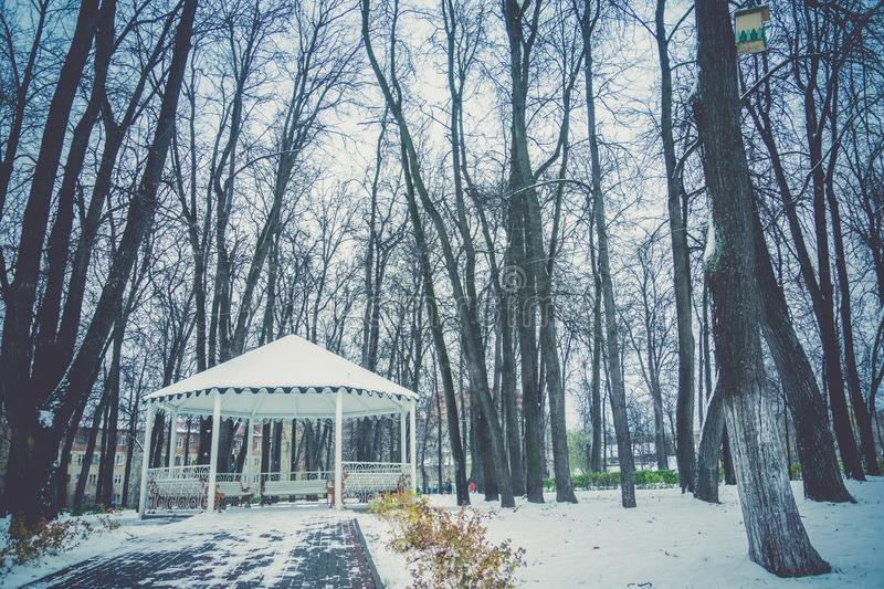 Winter White Alcove. Decorative wooden alcove with benches in the city park at the winter time stock photo