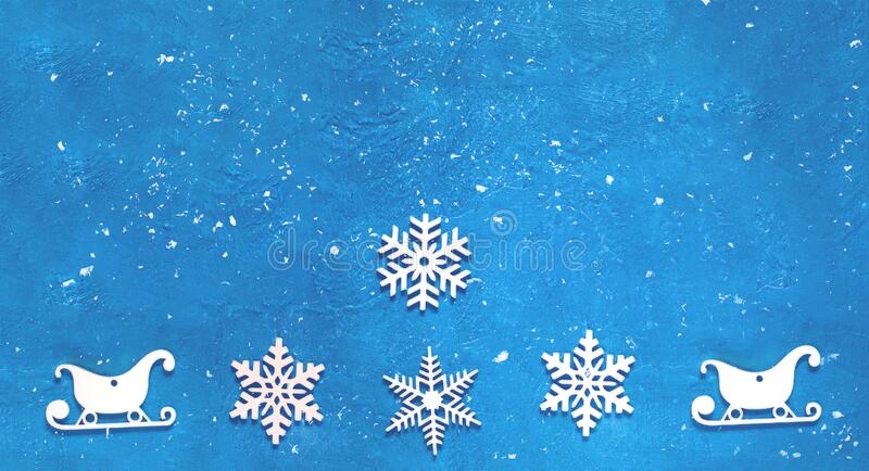 Decorative wooden Christmas snowflakes and sleighs on blue background. Festive New Year card in trendy color. Copy space stock photo