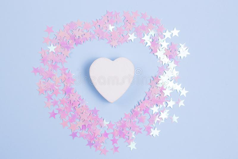 Decorative wooden heart with pink glitters on a pastel blue background.  royalty free stock photos