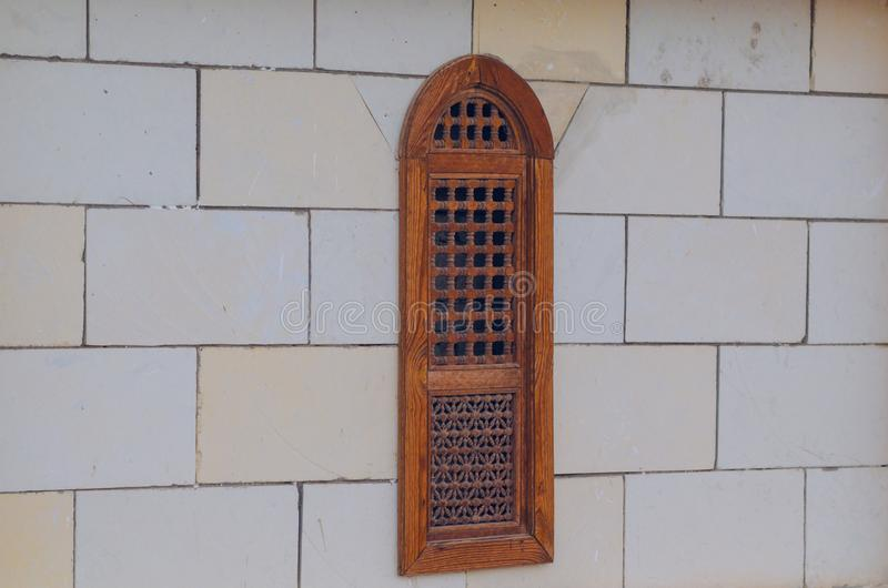 Decorative wooden window in the wall of foam concrete.  royalty free stock image