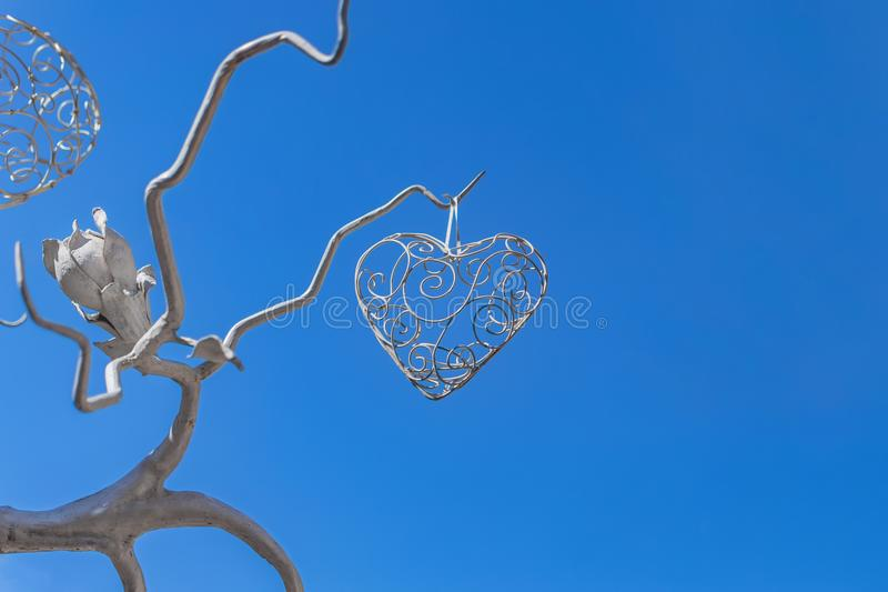 Decorative wrought iron wood with flower and heart openwork on a background of blue sky stock photo