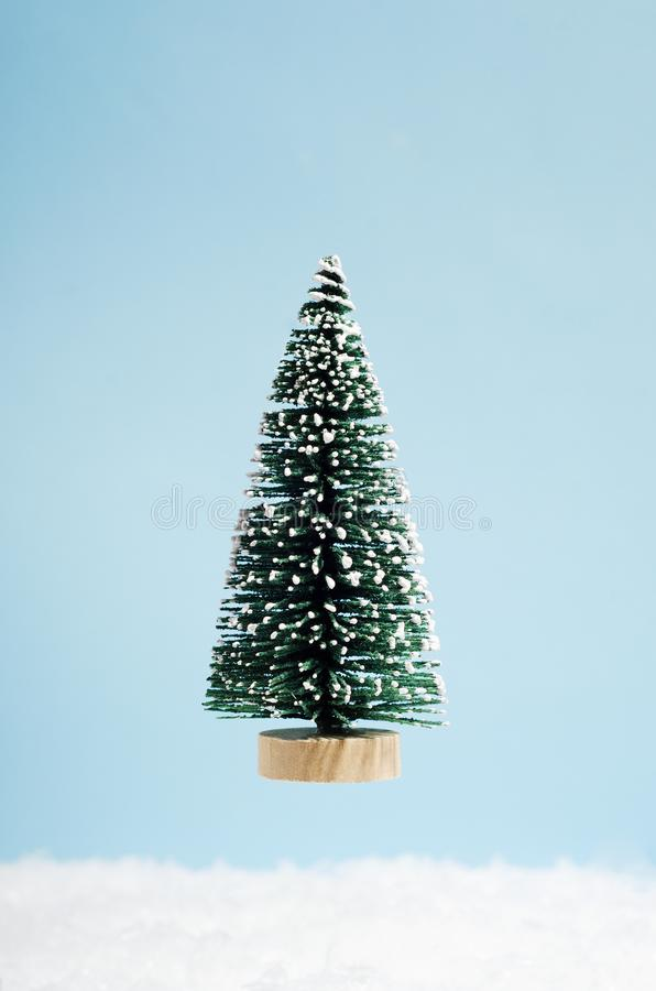 Decorative Xmas fir tree isolated on blue background. New year festive vertical backdrop. Christmas holiday creative greeting card stock photo