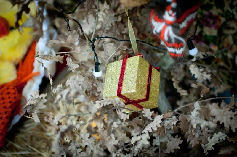Decorative yellow little gift as ornament on oak Christmas tree, royalty free stock images