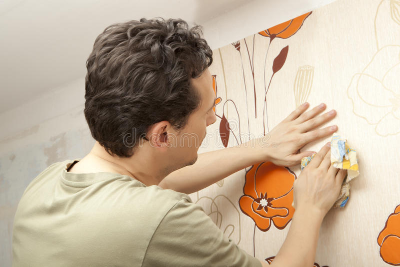Decorator hanging wallpaper. Repair and home concept royalty free stock image