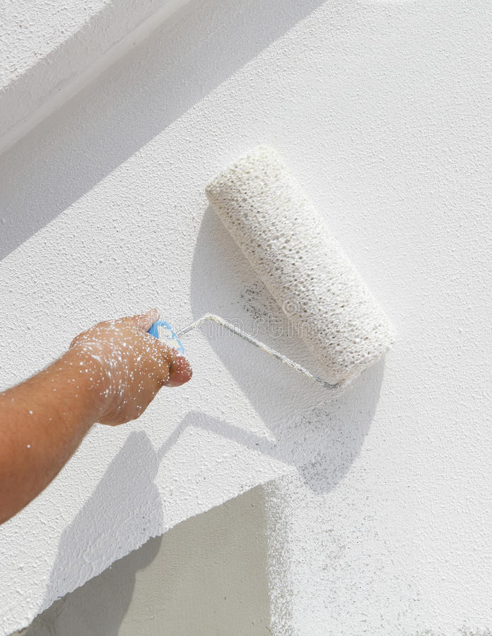 Decorator painting wall. Hand of a decorator painting a white wall with a roller stock photos