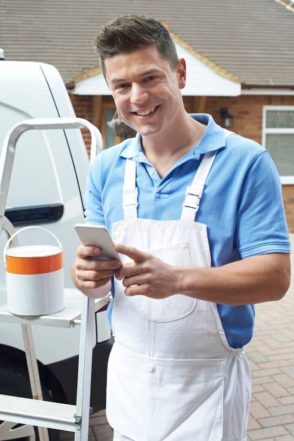 Decorator Używa telefon komórkowy pozycję Na zewnątrz Domowego domu zdjęcia royalty free