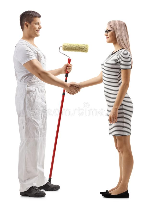 Decoratore maschio con un pittore del rullo che stringe le mani con una giovane donna fotografia stock