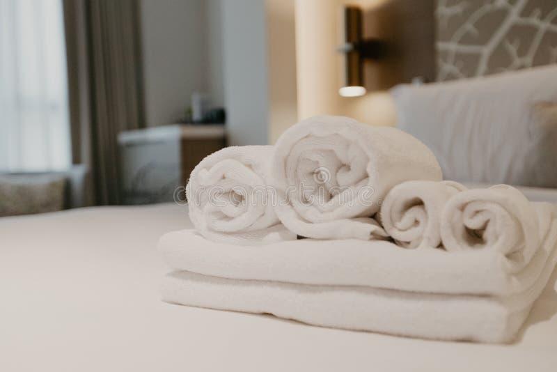 Decorazione bianca dell'asciugamano sull'interno della stanza del letto a letto fotografia stock libera da diritti