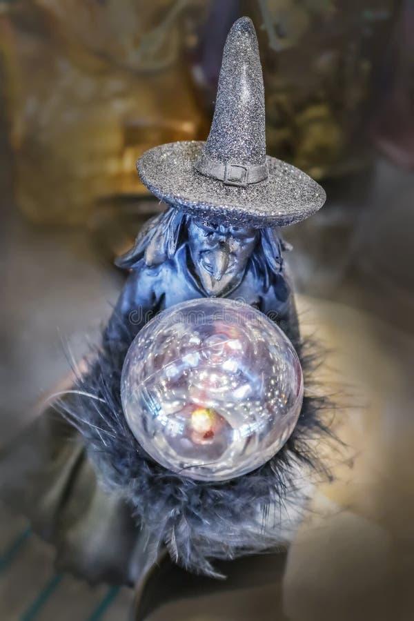 Decorazione cattiva di Halloween della strega con sfera di cristallo ed il cappello frizzante contro il fondo del bokeh fotografia stock