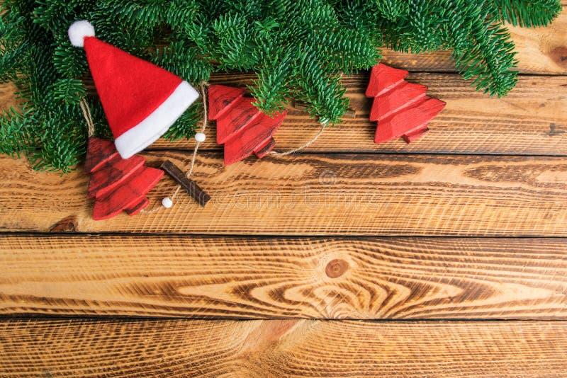 Decorazione d'annata di Natale con il ramo dell'abete e cappello di Santa su vecchio fondo di legno immagini stock libere da diritti