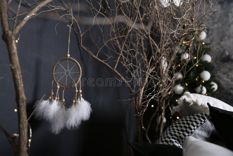 Decorazione dai rami di legno con un abete verde contro lo sfondo di Dreamcatcher con le piume bianche cuscini bianco-neri fotografia stock
