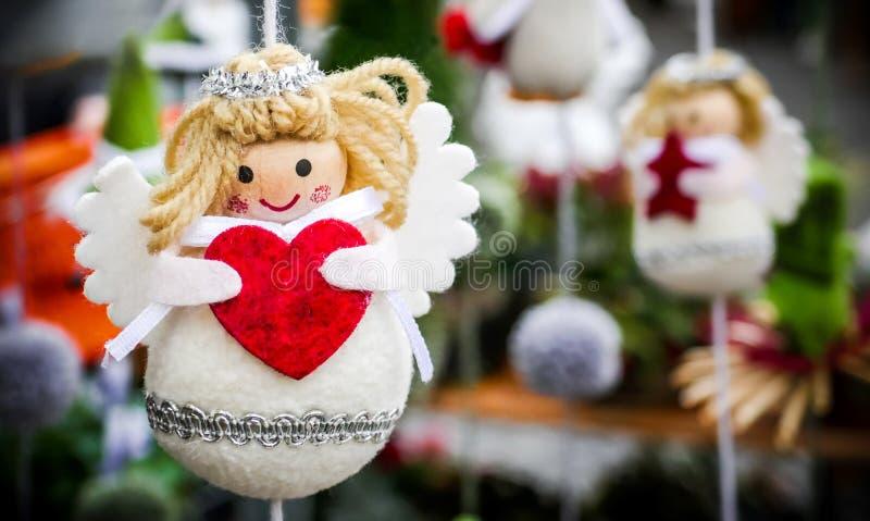 Decorazione dell'annata di inverno Natale o angelo d'attaccatura del biglietto di S. Valentino piccolo con un cuore rosso in sue  immagini stock