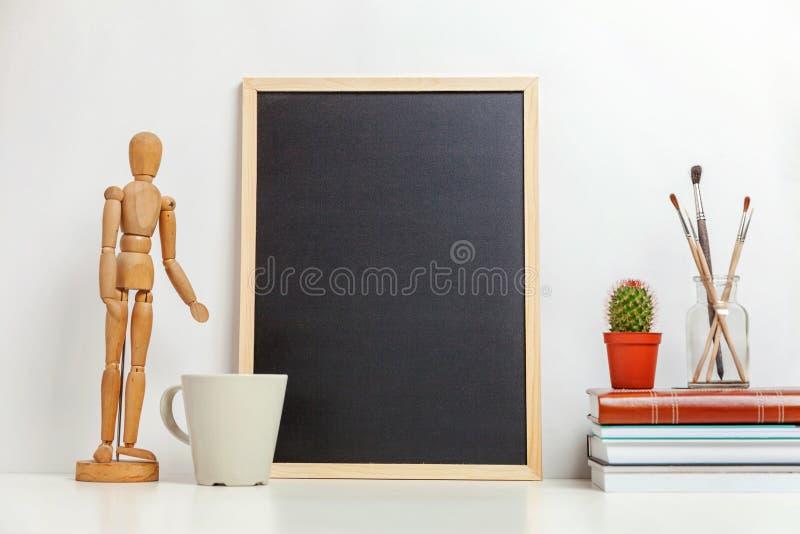 Decorazione dell'ufficio o della casa con derisione sulla lavagna in bianco sulla tavola vicino alla parete bianca fotografia stock libera da diritti