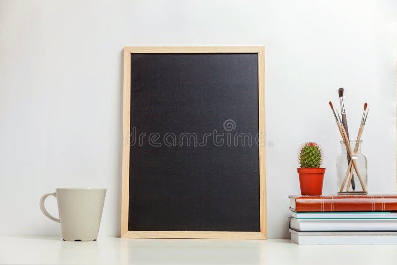 Decorazione dell'ufficio o della casa con derisione sulla lavagna in bianco sulla tavola vicino alla parete bianca fotografie stock