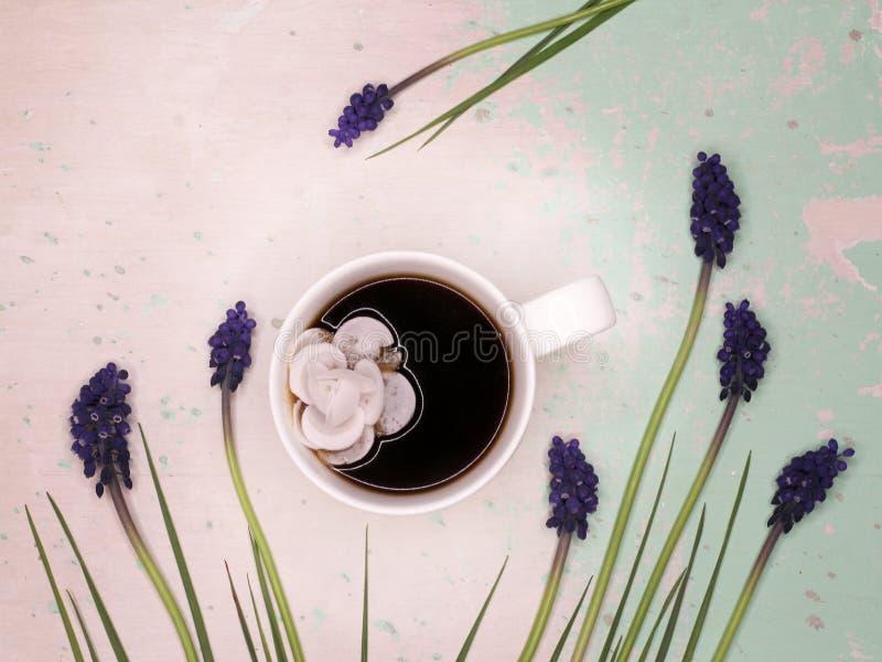 Decorazione della confetteria e della tazza da caffè circondata dai fiori della molla immagine stock libera da diritti