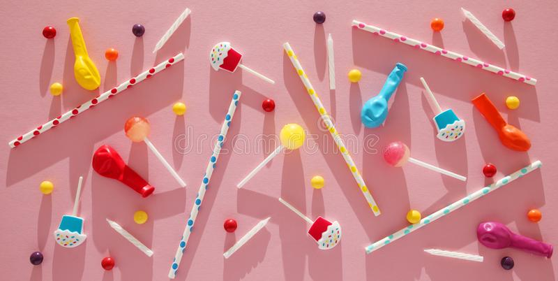 Decorazione della festa di compleanno dei bambini, modello rosa del fondo Caramelle variopinte, pallone luminoso, candele festive immagine stock