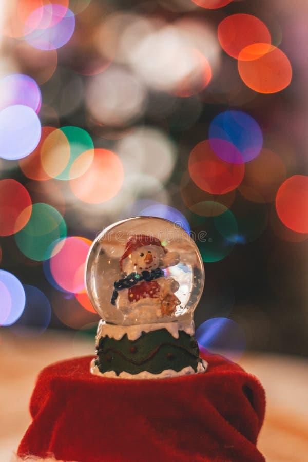 Decorazione della palla di vetro del pupazzo di neve con le luci di Natale nei precedenti fotografia stock