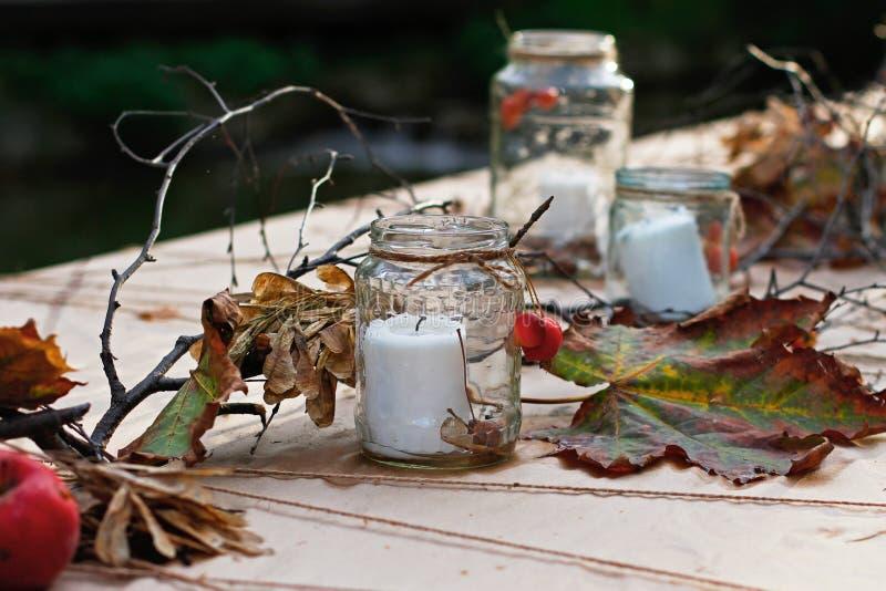 Decorazione della tavola di autunno con le candele in barattoli, foglie, rami e semi di vetro dell'acero fotografia stock libera da diritti