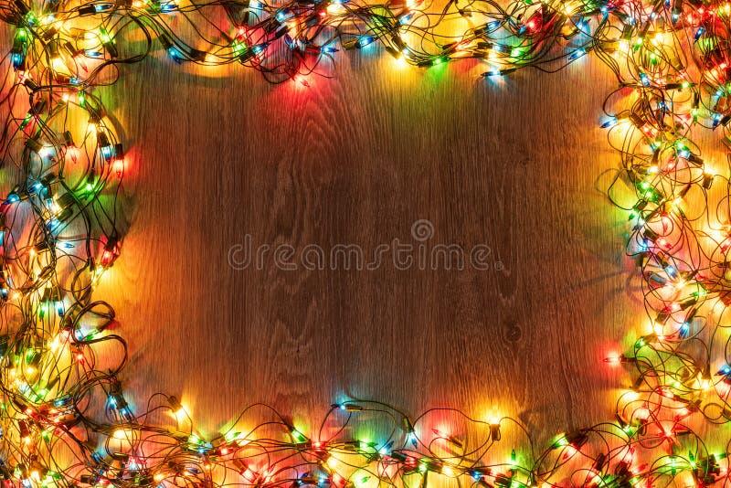 Decorazione delle luci Sfondo di legno con natale luci multicolori di garland In una cornice con spazio di copia per un testo immagine stock