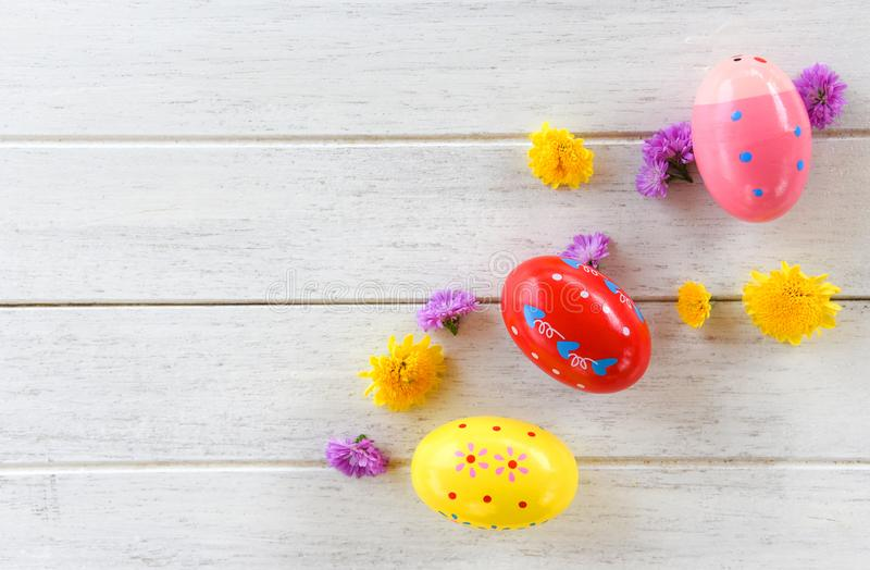 Decorazione delle uova di Pasqua con il fondo di legno bianco dei fiori variopinti fotografia stock