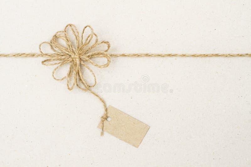 Decorazione di carta dell'arco dell'etichetta e della corda dell'etichetta, carta da imballaggio del regalo fotografie stock