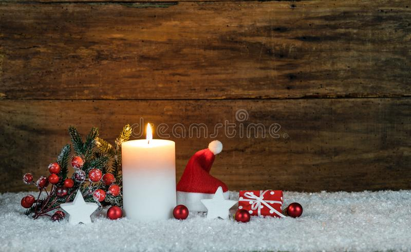 Decorazione di Natale con la candela, il cappello rosso di Santa ed il piccolo presente fotografia stock libera da diritti