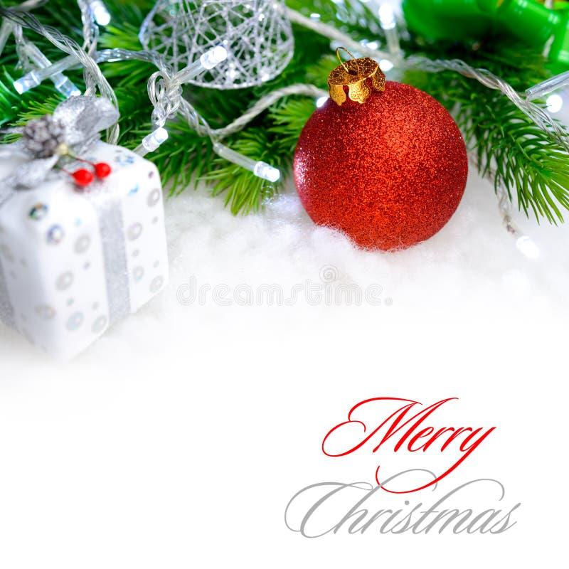 Decorazione di Natale con la palla rossa, il ramo verde dell'abete e le luci bianche in neve Cartolina d'auguri immagini stock libere da diritti
