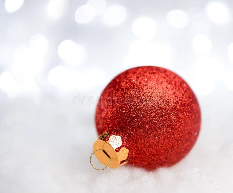 Decorazione di Natale con la palla rossa nella neve sui precedenti vaghi con le luci di festa Cartolina d'auguri immagini stock