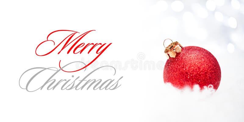 Decorazione di Natale con la palla rossa nella neve sui precedenti vaghi con le luci di festa Cartolina d'auguri immagini stock libere da diritti