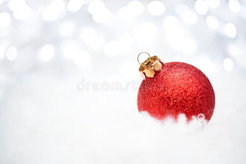 Decorazione di Natale con la palla rossa nella neve sui precedenti vaghi con le luci di festa Cartolina d'auguri immagine stock