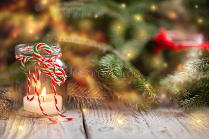 Decorazione di Natale con le candele in barattolo sul fondo di festa fotografia stock