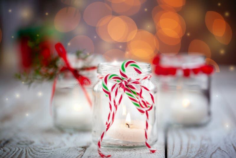 Decorazione di Natale con le candele in barattolo sul fondo di festa fotografia stock libera da diritti