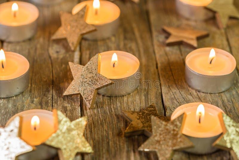 Decorazione di Natale con le candele e gli ornamenti dorati di forma della stella immagini stock