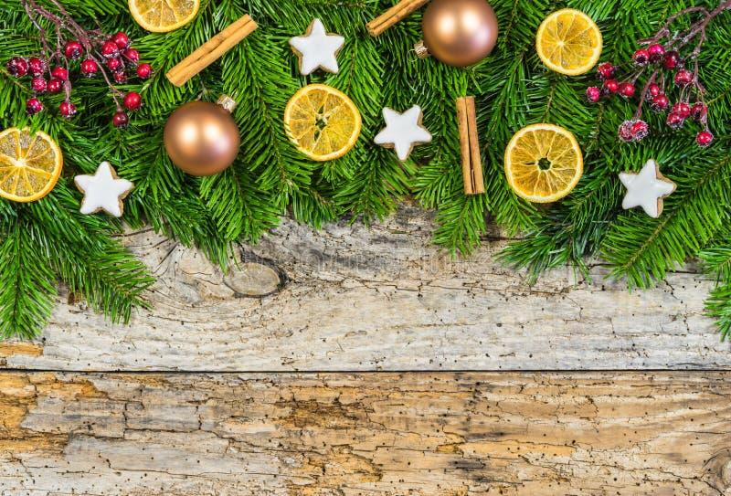 Decorazione di Natale con verde dell'abete ed ornamenti su vecchio legno fotografia stock