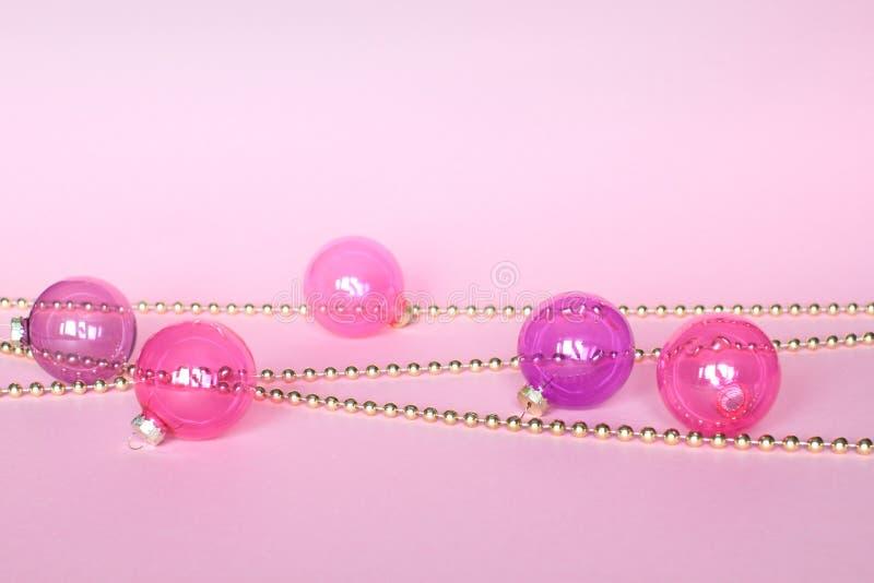 Decorazione di Natale di modo su fondo rosa Primo piano delle palle rosa di natale e delle perle dorate Cartolina d'auguri fotografie stock libere da diritti