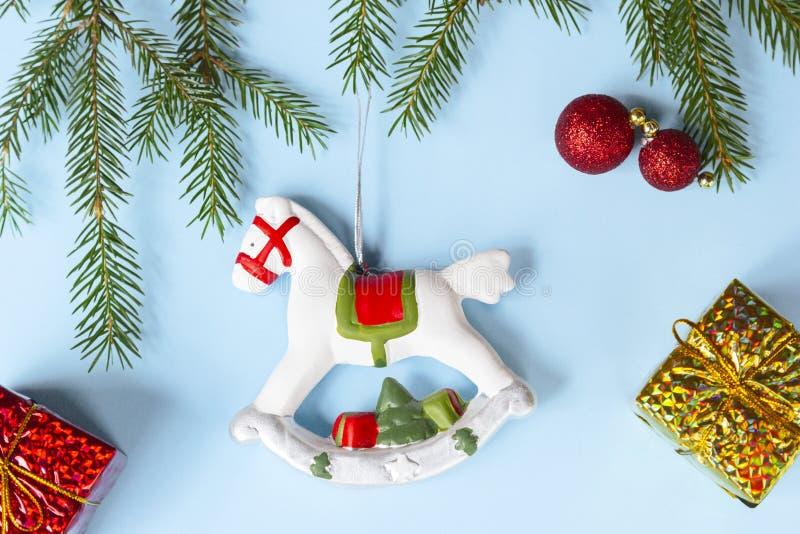 Decorazione di Natale - vecchio cavallo a dondolo, rami dell'abete, regali dorati, palle rosse di Natale su fondo blu Feste di co fotografie stock
