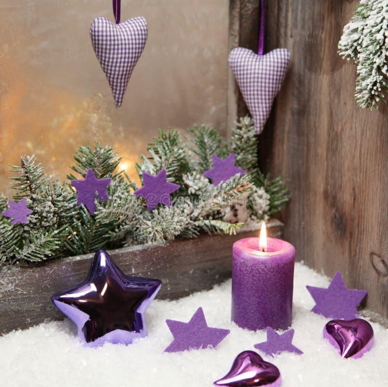 Decorazione di Natale in viola o in porpora con legno e una candela immagine stock