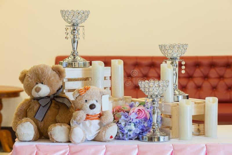 Decorazione di nozze con i dolci, gli orsi del giocattolo, gli anelli e candlestic immagini stock libere da diritti
