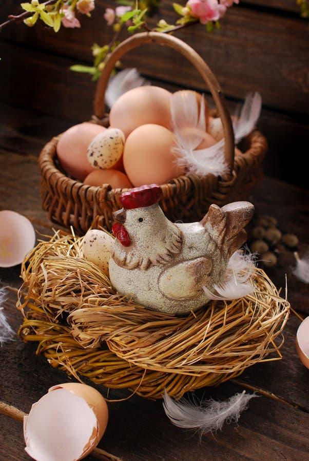 Decorazione di Pasqua della gallina nel nido e del canestro di vimini con le uova fotografia stock libera da diritti