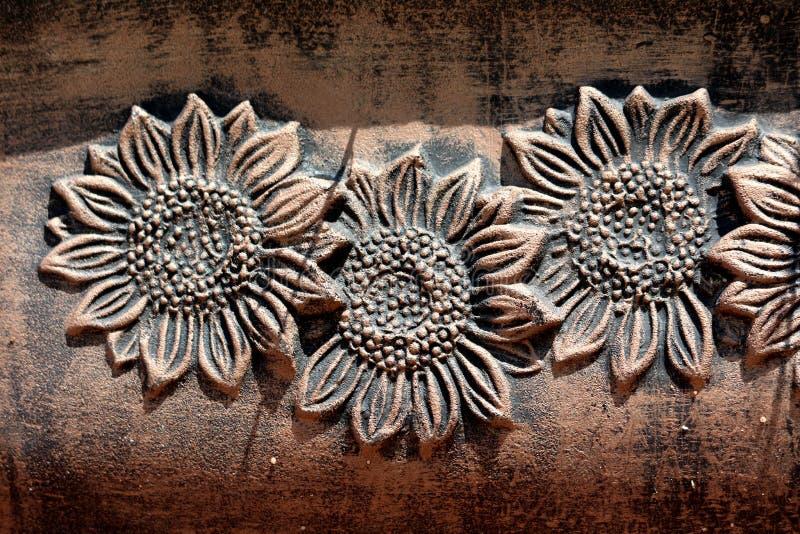 Decorazione di plastica del vaso di fiore in una forma di tre fiori aperti fatti per somigliare ai vasi concreti antichi in giard fotografia stock