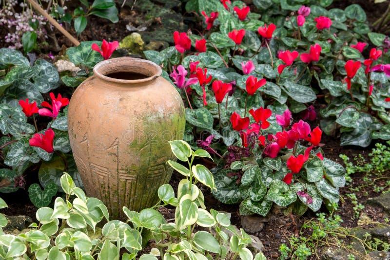 Decorazione di terra del barattolo nei precedenti del giardino fotografia stock