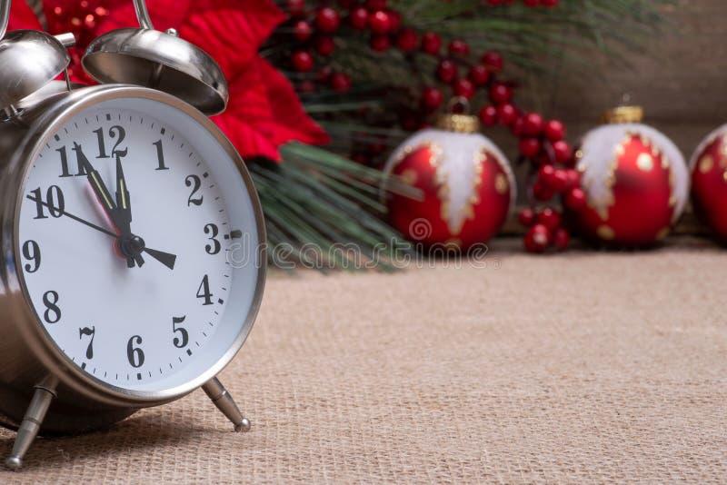 Decorazione di vacanza invernale, concetto del nuovo anno e di Natale con la sveglia: Stella di Natale rossa, pino, cespuglio del fotografie stock