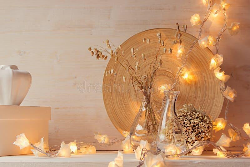 Decorazione domestica molle con le luci brucianti su fondo di legno bianco fotografie stock libere da diritti