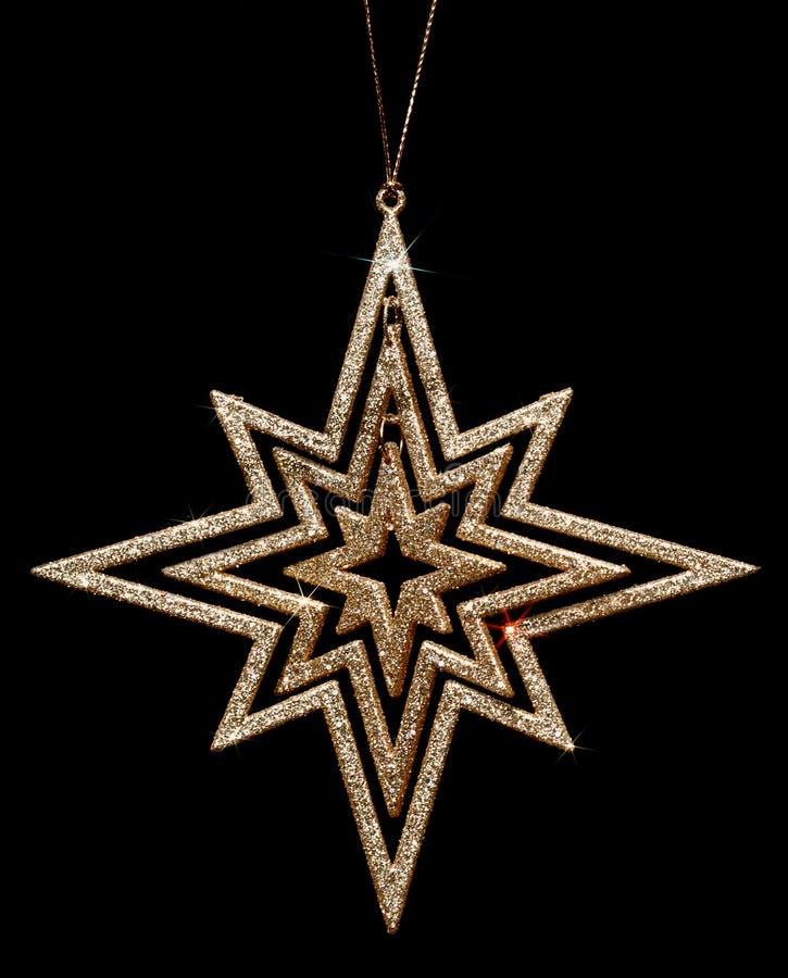 Decorazione dorata della stella di natale di scintillio sul nero immagine stock