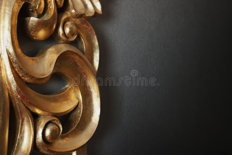 Decorazione dorata sulla parete scura immagini stock