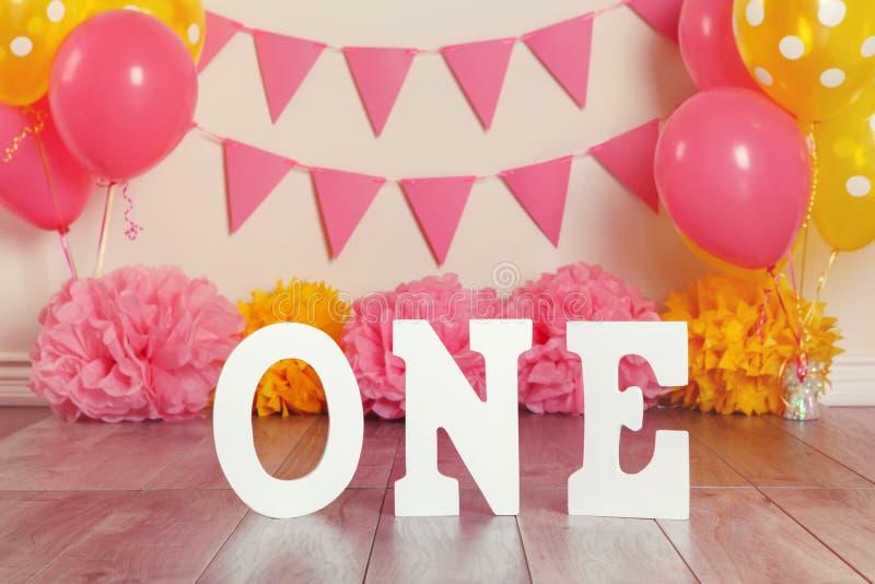 Decorazione festiva del fondo per la celebrazione di compleanno con le lettere che dicono uno ed i palloni gialli rosa-rosso fotografia stock