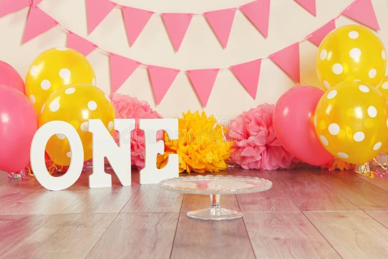 Decorazione festiva del fondo per la celebrazione di compleanno con le lettere che dicono uno ed i palloni gialli rosa-rosso fotografie stock libere da diritti