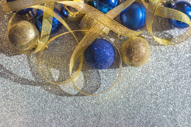Decorazione festiva delle palle del nuovo anno e di Natale e dei nastri dorati blu dell'oro fotografia stock
