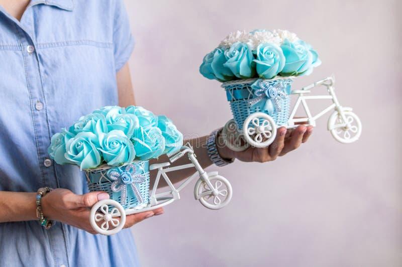 Decorazione floreale festiva: due piccoli canestri decorativi sotto forma di forbicycle con i germogli di fiore blu nelle mani de immagini stock